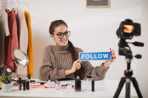 A female content creator holds up a FOLLOW sign in front of a camera.