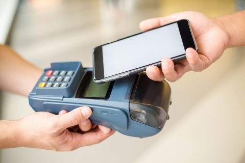 Cell phone tapping on payment machine.