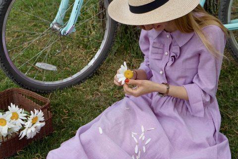 Woman plucks petals off a daisy in a grassy park.